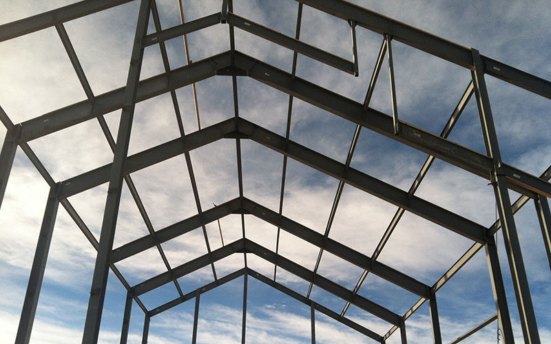 metal bars forming a pointed roof against a blue sky
